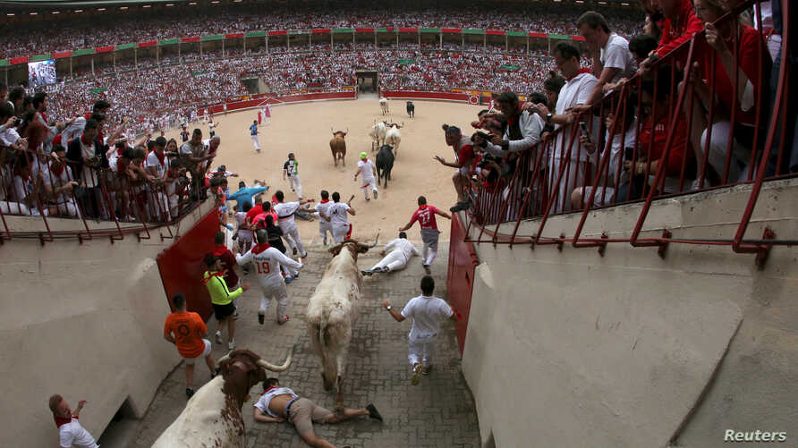 Revelers fall as they enter the bullring following the first running of the bulls at the San Fermin festival in Pamplona, Spain, July 7, 2019.