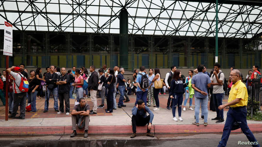 People wait for transportation outside a closed metro station during a blackout in Caracas, Venezuela, July 22, 2019.