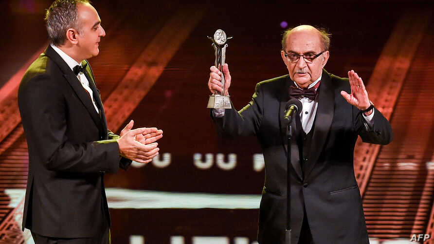 Egyptian film critic Youssef Cherif Rizkallah (R) appears on-stage alongside Cairo International Film Festival (CIFF) President Mohamed Hefzi, as the former receives an award during the opening ceremony of the festival's 40th edition at the Cairo Opera House, Nov. 20, 2018.