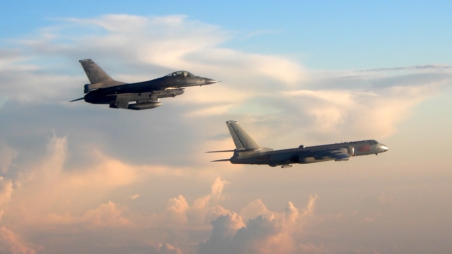FILE - This photo taken May 25, 2018, by Taiwan's Defense Ministry shows Taiwan's F-16 fighter jet, left, monitoring one of two