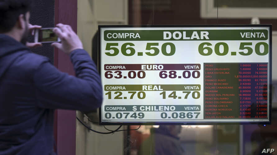 Currency exchange values are displayed on the buy-sell board of a bureau de exchange in Buenos Aires, Aug. 14, 2019.