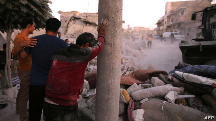 People react following a reported airstrike by Syrian regime forces in the town of Maaret al-Numan in Syria's northwestern Idlib province, Aug. 28, 2019.