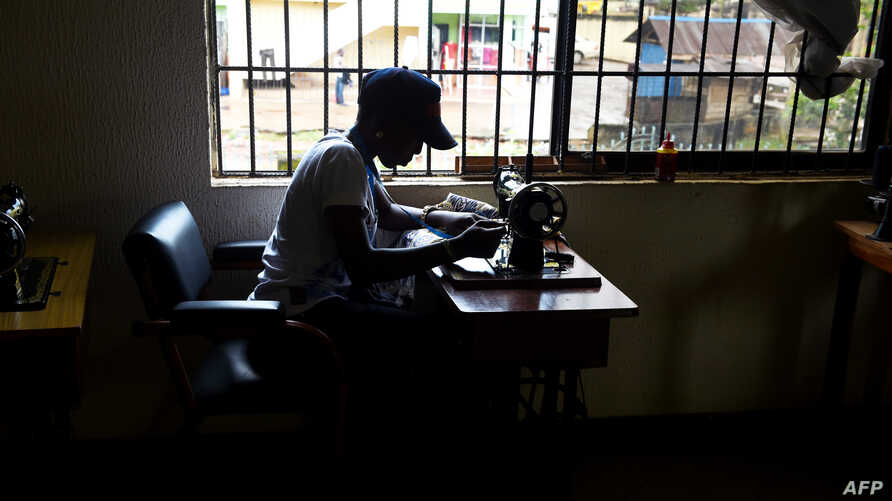 FILE - A victim of human trafficking in Libya sews clothes in Benin, Edo State, Nigeria, Oct. 21, 2016. Human Rights Watch says in a new report that Nigerian trafficking survivors are not getting enough support from their government.