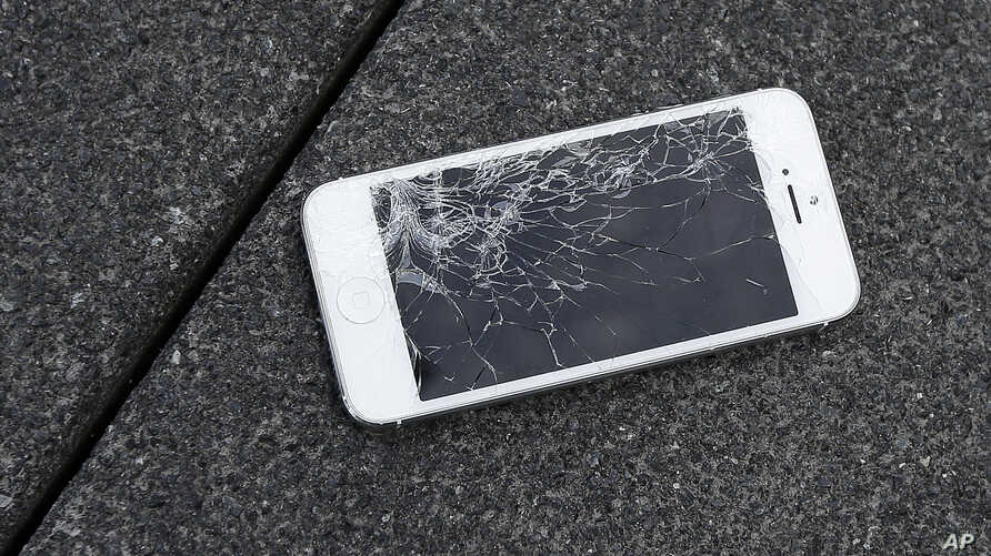 FILE - An Apple iPhone with a cracked screen after a drop test is seen at the offices of SquareTrade in San Francisco.