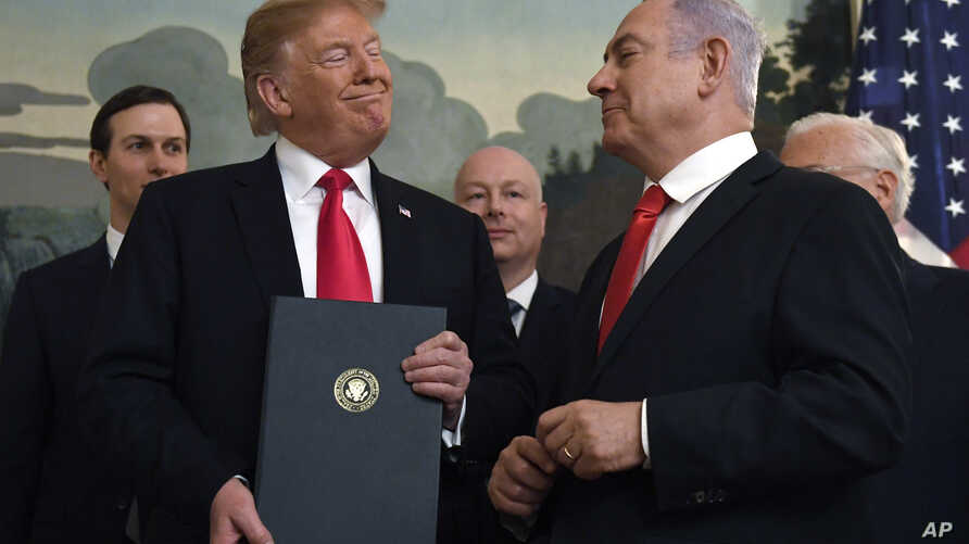 FILE - In this March 25, 2019 file photo, President Donald Trump smiles at Israeli Prime Minister Benjamin Netanyahu, right, after signing a proclamation at the White House in Washington.