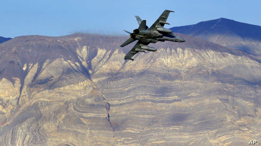FILE - An F/A-18D Hornet flies out of what is known as Star Wars Canyon in Death Valley National Park, Calif., Feb. 27, 2017. On July 31, 2019, a U.S. Navy F/A-18 Super Hornet jet crashed in the California desert, killing the pilot.