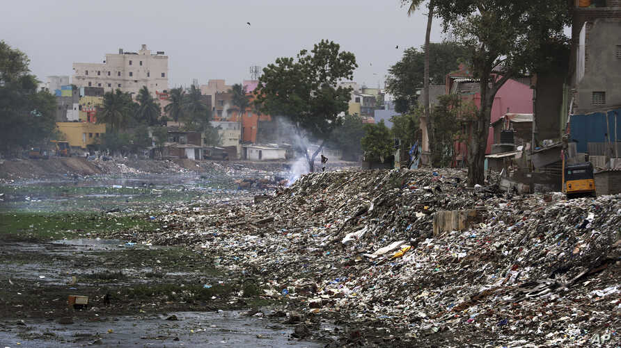 In this July 20, 2019, photo, a homeless person burns garbage in the polluted river Cooum in Chennai in Southern Indian state of Tamil Nadu.