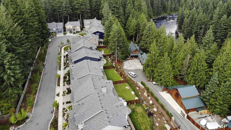 In this photo taken July 24, 2019, a block of houses are carved into a forest along the Middle Fork Snoqualmie River in the Cascade foothills of North Bend, Wash.