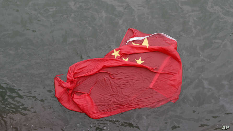 A Chinese flag floats on the surface it was thrown in the water by protesters during a demonstration in Hong Kong, Saturday, Aug. 3, 2019.