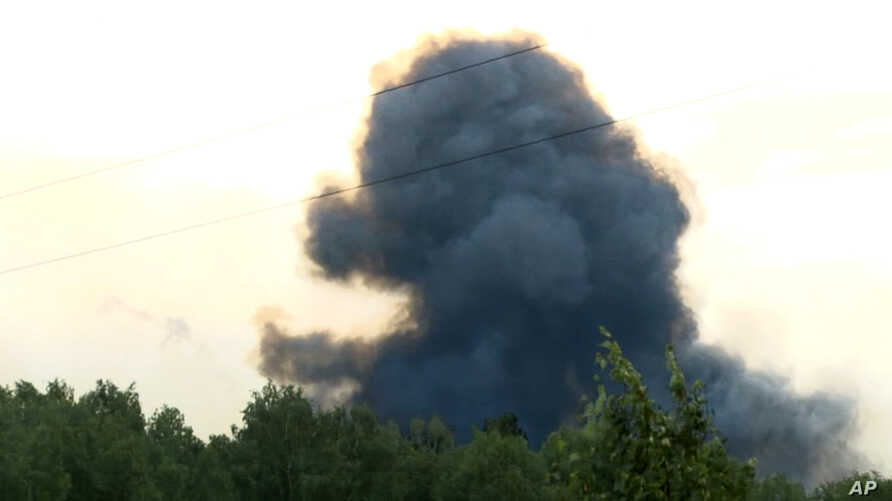 In this video grab provided by the RU-RTR Russian television, smoke rises after explosions at the military base, about 10 kilometers from Achinsk, Krasnoyarsk region, Russia Far East, Aug. 5, 2019.