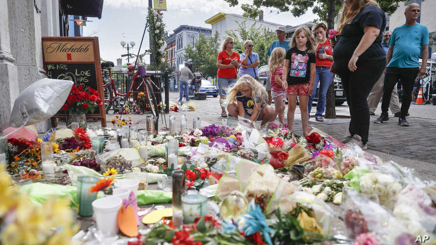 Mourners bring flowers to a makeshift memorial Aug. 6, 2019, for the slain and injured in the Oregon District after a mass shooting early Sunday in Dayton, Ohio.