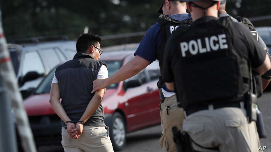 A man is taken into custody at a Koch Foods Inc. plant in Morton, Miss., Aug. 7, 2019.