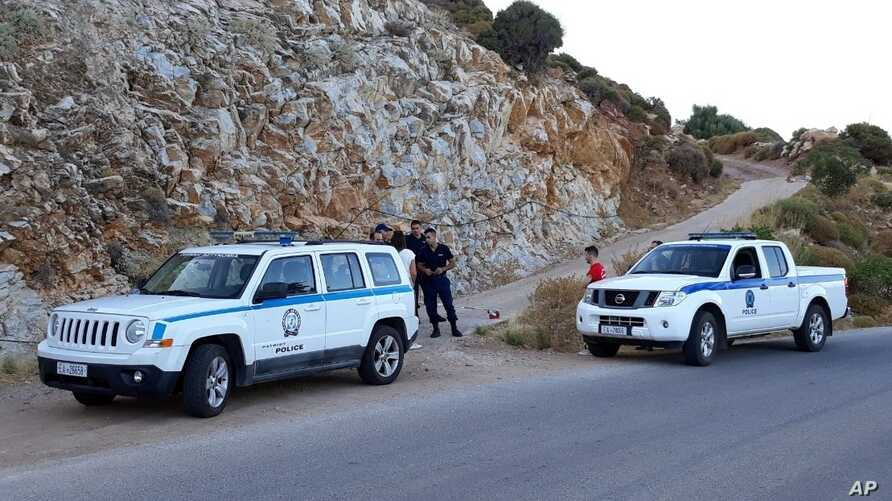 Authorities block a road near the location where police said the body of Cyprus-based astrophysicist Natalie Christopher, 34, was found in a 20-meter-deep ravine, in Faros village on the Greek island of Ikaria, Wednesday, August 7, 2019.