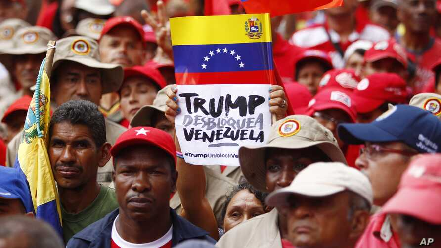 "A demonstrator holds a sign with a message that reads in Spanish: ""Trump unblock Venezuela"" as members of the Bolivarian militia attend a protest against U.S. sanctions on Venezuela, in Caracas, Venezuela, Aug. 7, 2019."
