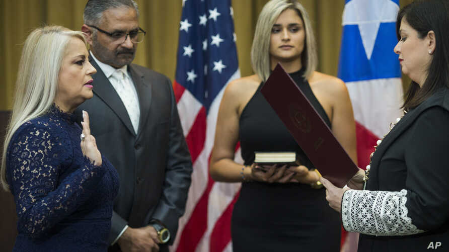 Justice Secretary Wanda Vazquez is sworn in as governor of Puerto Rico by Supreme Court Justice Maite Oronoz, in San Juan, Aug. 7, 2019.  Vazquez was joined by her daughter Beatriz Diaz Vazquez and her husband Judge Jorge Diaz.