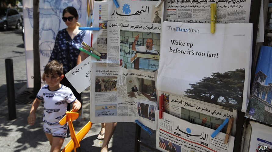 People walk past a shop selling newspapers in Beirut, Lebanon, Aug. 8, 2019.