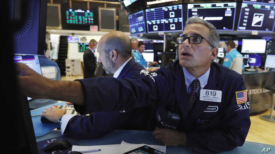 Specialist Anthony Rinaldi, right, works at his post on the floor of the New York Stock Exchange, Aug. 8, 2019.
