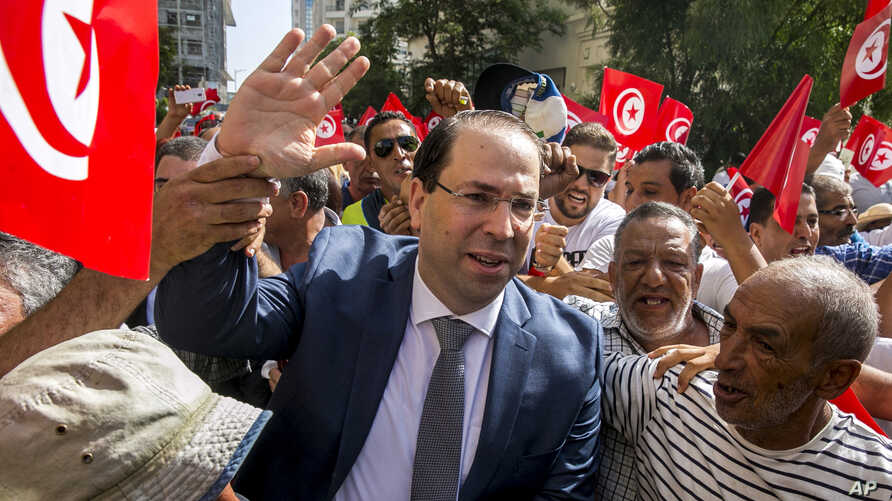 FILE - Tunisian Prime Minister Youssef Chahed, center, arrives to submit his candidacy for the upcoming early presidential elections in Tunis, Tunisia, Aug. 9, 2019.