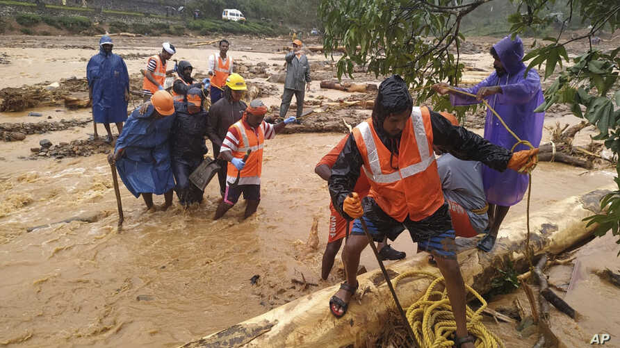 In this handout photo provided by the National Disaster Response Force (NDRF), NDRF personnel help move flood victims to safer areas in Wayanad district, in the southern Indian state of Kerala.