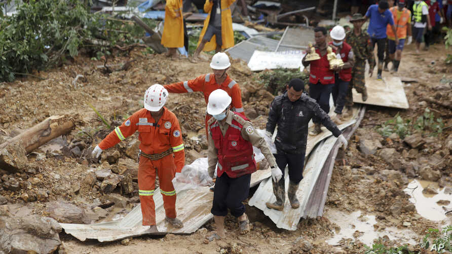 Members of a Myanmar rescue team carry a body at a landslide-hit area in Paung township, Mon State, Myanmar Saturday, Aug. 10, 2019.