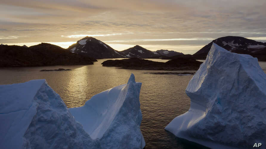 An aerial view of large Icebergs floating as the sun rises near Kulusuk, Greenland, early Friday, Aug. 16, 2019.