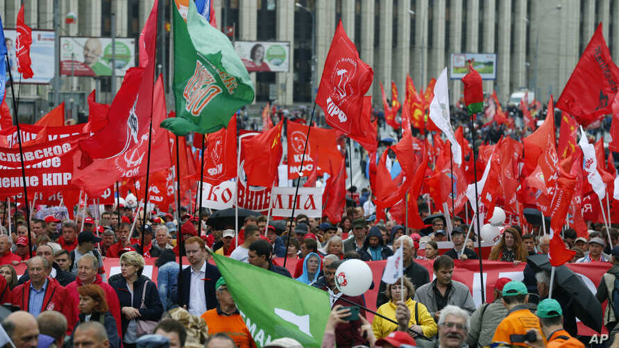 Communist party supporters wave red flags during a protest in the center of Moscow, Russia, Saturday, Aug. 17, 2019. People rallied Saturday against the exclusion of some city council candidates from Moscow's upcoming election.