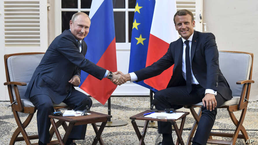 French President Emmanuel Macron, right, shakes hands with Russian President Vladimir Putin after their meeting at the fort of Bregancon in Bormes-les-Mimosas, southern France, Aug. 19, 2019.