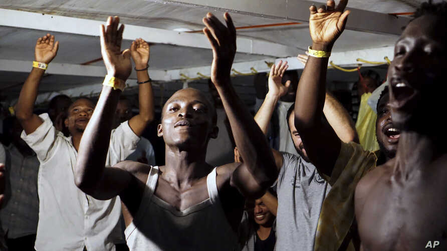 Migrants onboard the Open Arms vessel celebrate the news of an Italian prosecutor who has ordered that the migrants be disembarked on the island of Lampedusa, southern Italy, Aug. 20, 2019.