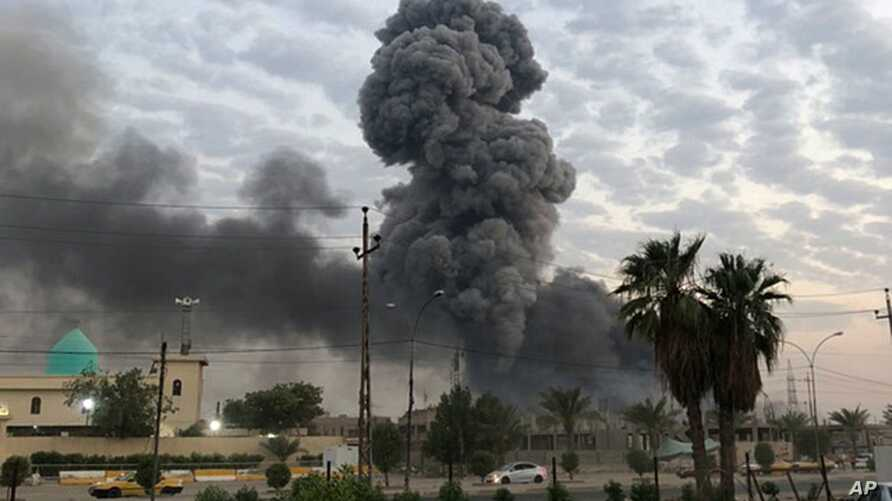 Plumes of smoke rise after an explosion at a military base southwest of Baghdad, Iraq, Aug. 12, 2019