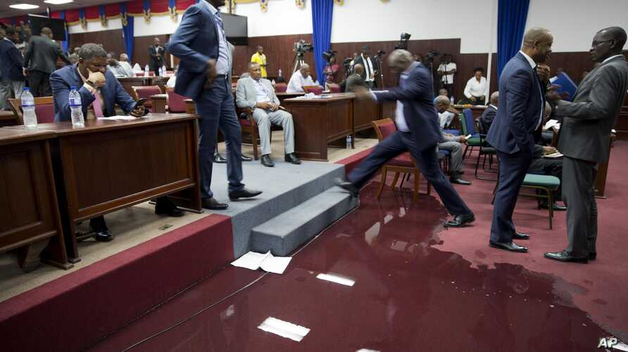 A lawmaker steps over a large puddle of water on the Parliament floor, created by rain water leaking through the roof, as lawmakers meet to debate whether or not to start impeachment proceedings for Haitian President Jovenel Moise in Port-au-Prince, Haiti, Wednesday, Aug. 21, 2019.