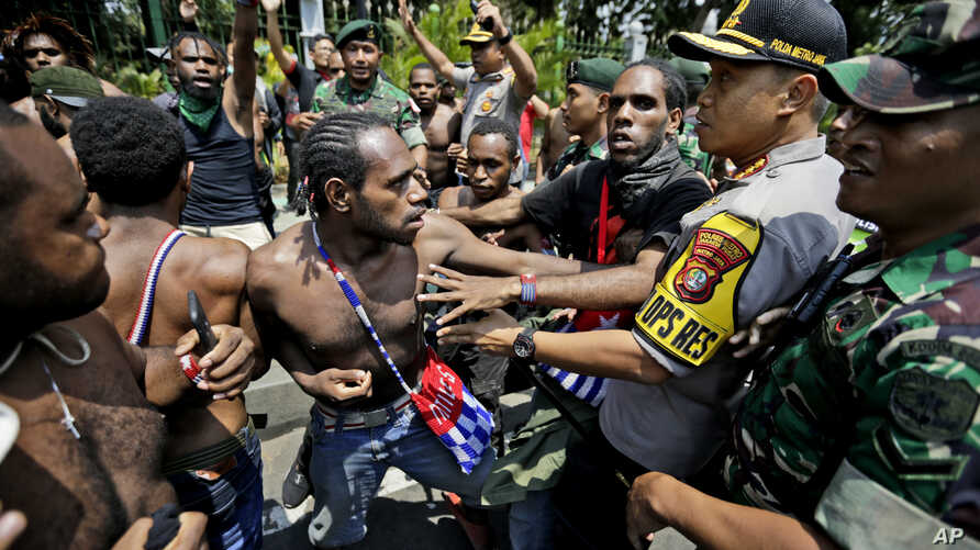 Papuan activists scuffle with police and soldiers during a rally near the presidential palace in Jakarta, Indonesia, Thursday, Aug. 22, 2019.