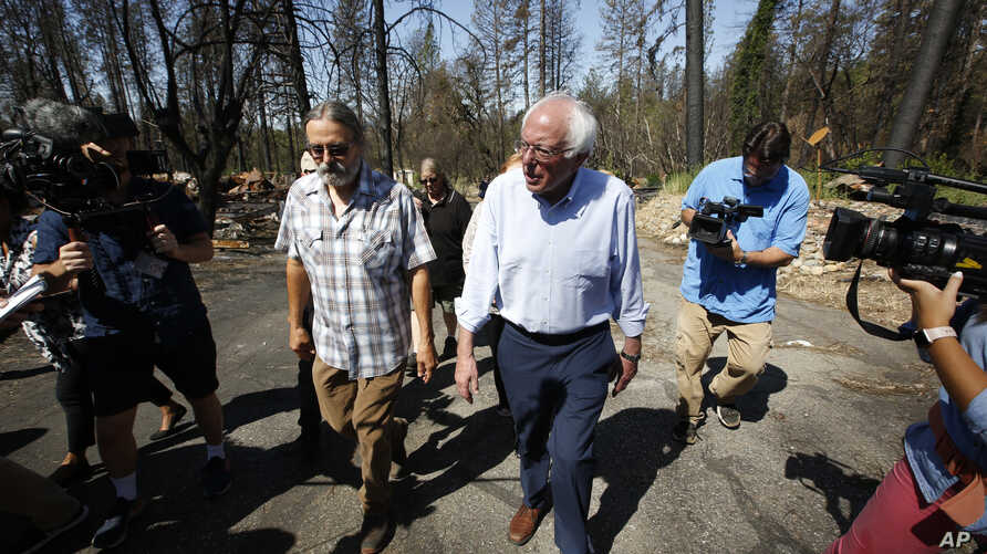 FILE - Democratic presidential candidate Sen. Bernie Sanders, I-Vermont (R) talks with area resident Michael Ranney as he tours a mobile home park that was destroyed by last year's wildfire in Paradise, Calif., Aug. 22, 2019.