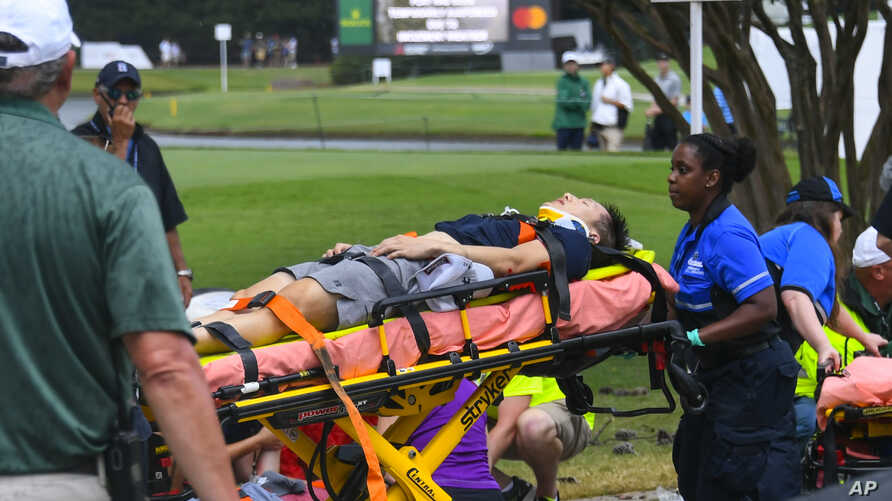A spectator is taken to an ambulance after a lightning strike at East Lake Golf Club during a weather delay in the third round of the Tour Championship golf tournament, Aug. 24, 2019, in Atlanta.