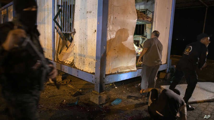 Palestinians check a damaged police container following an explosion targeted a Hamas police checkpoint in Gaza City, Aug. 28, 2019.