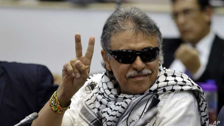 FILE - Former FARC rebel Seuxis Hernandez, also known as Jesus Santrich, flashes a victory sign at journalists as he attends a session of the Chamber of Representatives at the Colombian congress in Bogota, Colombia, June 12, 2019.