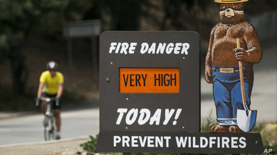 """FILE - A Smokey Bear """"Very High"""" fire danger sign is posted at the entrance to Griffith Park in Los Angeles, Sept. 10, 2015."""