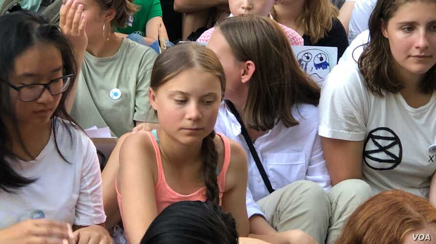 Young climate activist Greta Thunberg, center, listens during a rally outside the United Nations in New York to demand action on global warming, Aug. 30, 2019. (M. Besheer/VOA)