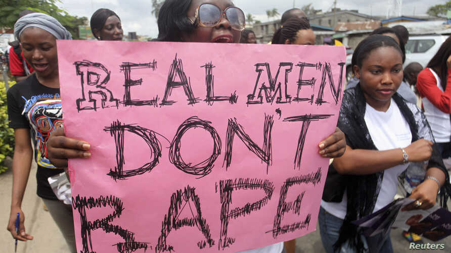 "FILE - A woman carries a placard as she shouts a slogan during the ""Walk Against Rape'"" procession organized by Project Alert, a"