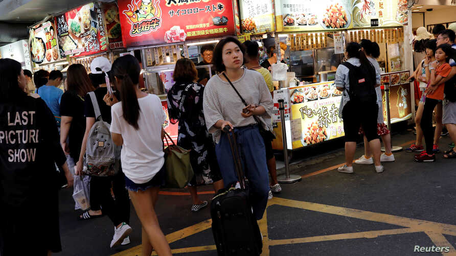 FILE - Tourists walk near food stalls at Ximending shopping district in Taipei, Taiwan.