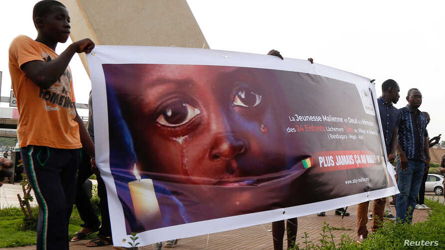 FILE - People carry a banner during a remembrance ceremony for the children who were killed during an attack on the Dogon village of Sobane Da, at the Monument de la Paix in Bamako, Mali, June 15, 2019.