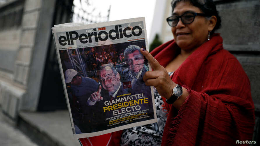 A woman reads a newspaper with a picture of presidential candidate Alejandro Giammattei, the winner of the presidential election, in Guatemala City, Guatemala, Aug. 12, 2019.