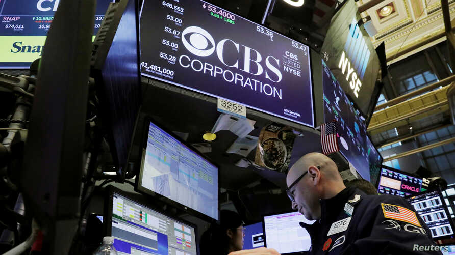 FILE - A trader works below the CBS Corporation logo on the floor of the New York Stock Exchange in New York.