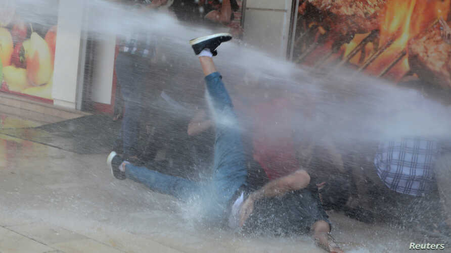 Turkish police use a water cannon to disperse demonstrators during a protest against the replacement of Kurdish mayors with state officials in three cities, in Diyarbakir, Aug. 19, 2019.