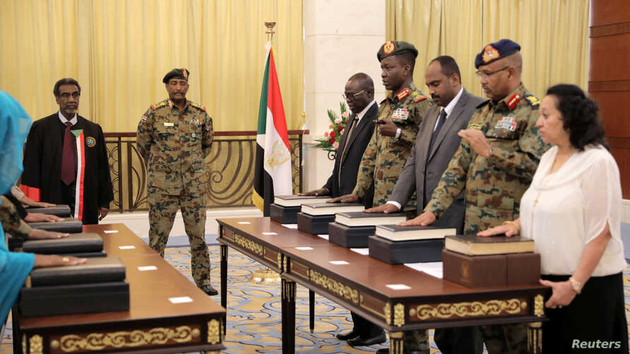 The leader of Sudan's transitional council looks on as military and civilian members of Sudan's new ruling body, the Sovereign Council, are sworn in at the presidential palace in Khartoum, Sudan, Aug. 21, 2019.