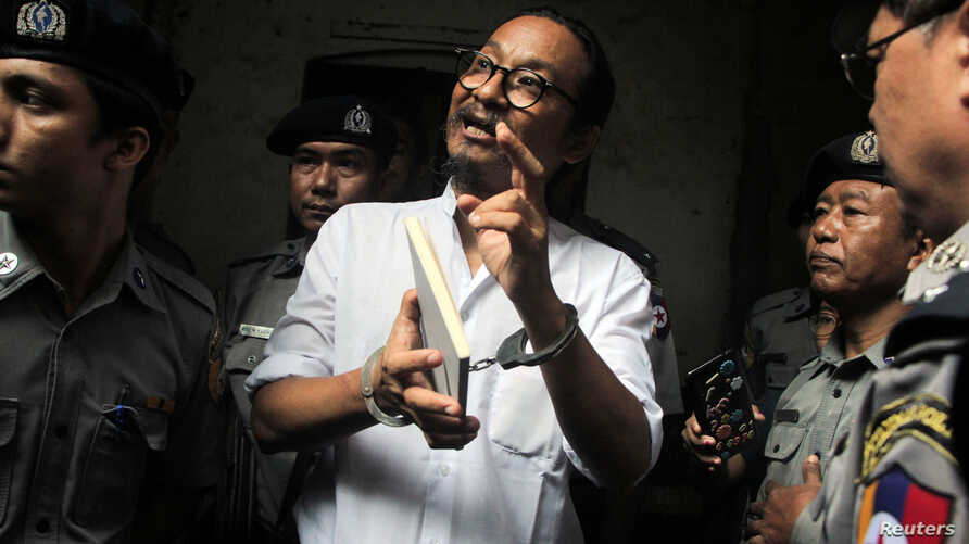 Filmmaker Min Htin Ko Ko Gyi is escorted out by police after a court hearing in Yangon, Myanmar, Aug. 29, 2019.