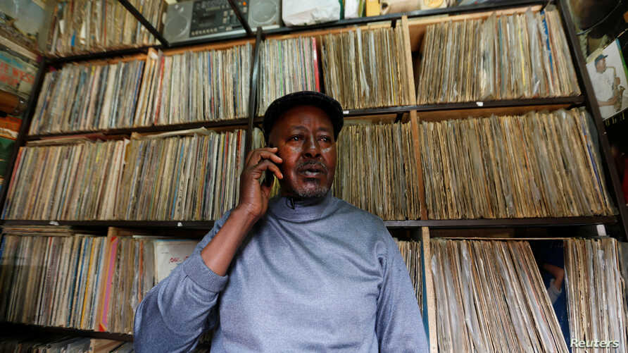 Vendor James Rugami talks to a customer on his cell phone inside his shop that specialize in selling second-hand vinyl records and vintage players at the Kenyatta Market in Nairobi, Kenya Nov. 24, 2016.