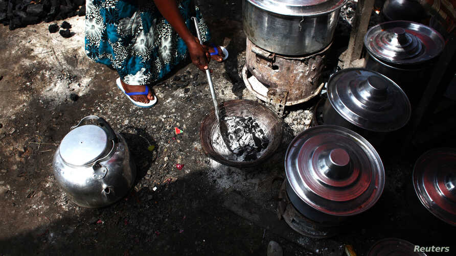 FILE - A woman adjusts the charcoal in a stove next to cooking pots at a village about 30 km (19 miles) south of South Sudan's capital Juba, June 21, 2013.
