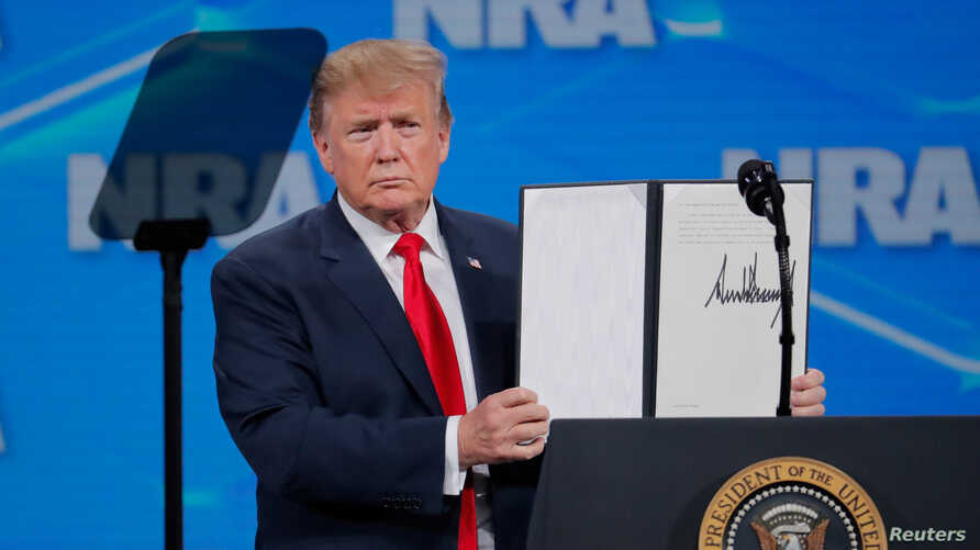 U.S. President Donald Trump holds up an executive order with his signature as he announces that the United States will drop out of the Arms Trade Treaty signed during the Obama administration during a speech in Indianapolis, Indiana, April 26, 2019.