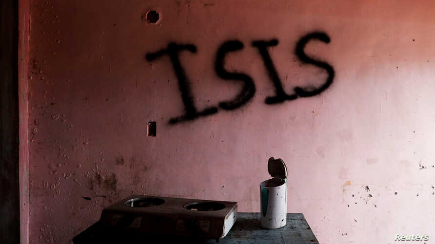 """Burned kitchen items are seen in front of a wall spray-painted with the word """"ISIS"""" in a home in the most affected war-torn area of Marawi City, Lanao province, Philippines, May 11, 2019."""