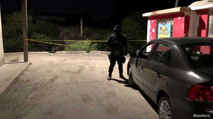 A police officer keeps watch at a scene after a migrant from Central America was gunned down near a train station in Saltillo, Mexico July 31, 2019.